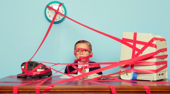A young boy and businessman is all tied up in rules, regulations and unrealistic expectations. The boy is all taped up with red tape. His business is stuck in red tape and unable to perform. Retro styled.